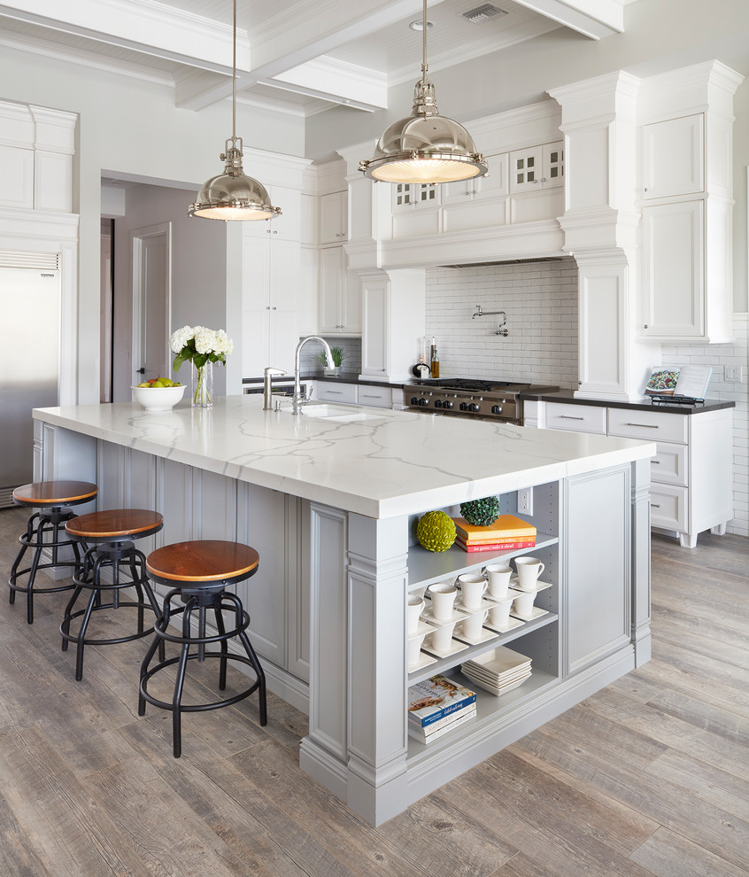 Open concept kitchen - large traditional l-shaped ceramic tile and brown floor open concept kitchen idea in Phoenix with an undermount sink, recessed-panel cabinets, white cabinets, quartz countertops, white backsplash, ceramic backsplash, stainless steel appliances and an island
