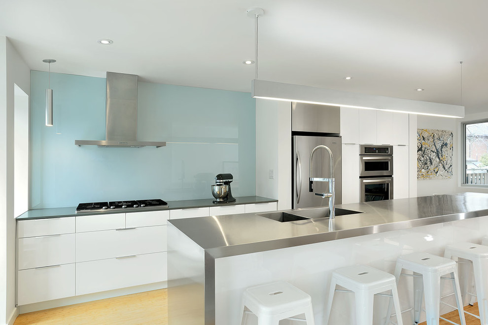 Trendy galley kitchen photo in Toronto with an integrated sink, flat-panel cabinets, white cabinets, stainless steel countertops, blue backsplash, glass sheet backsplash and stainless steel appliances