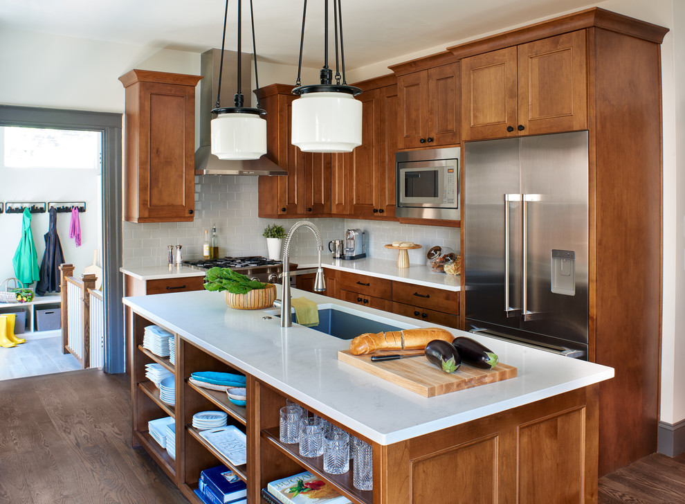 Example of a small arts and crafts l-shaped medium tone wood floor and brown floor eat-in kitchen design in Denver with an undermount sink, shaker cabinets, medium tone wood cabinets, quartz countertops, gray backsplash, subway tile backsplash, stainless steel appliances and an island