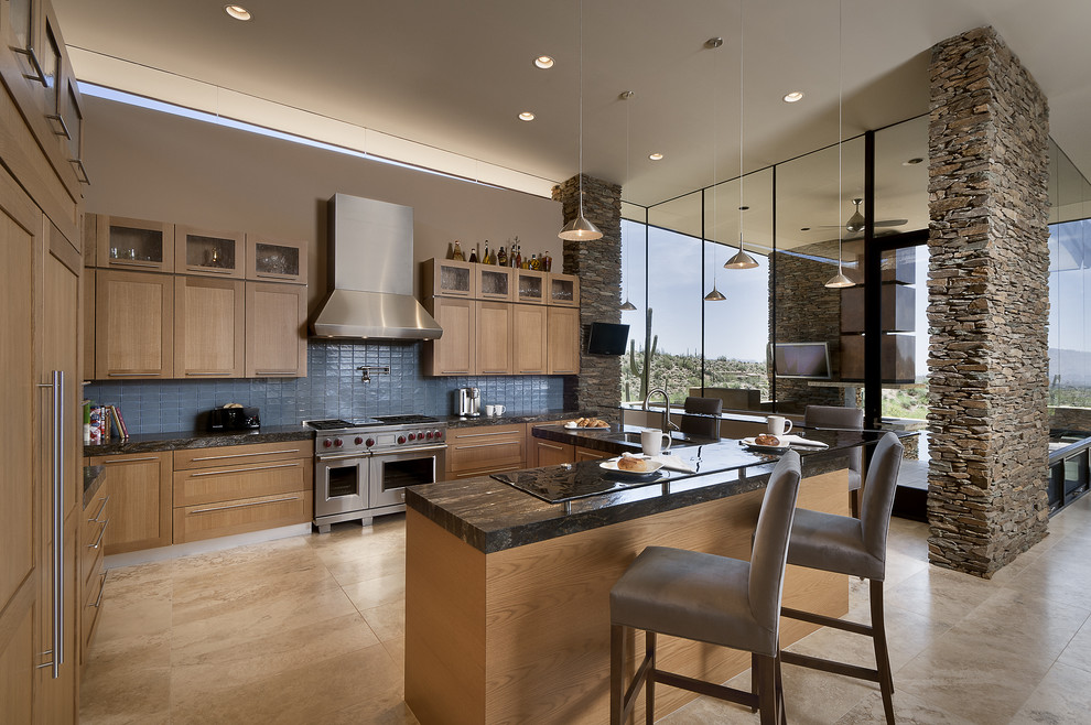 Inspiration for a large southwestern l-shaped travertine floor and beige floor open concept kitchen remodel in Phoenix with stainless steel appliances, shaker cabinets, medium tone wood cabinets, granite countertops, blue backsplash, an undermount sink, glass tile backsplash and two islands