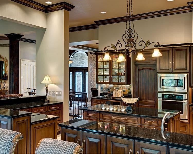 Eat-in kitchen - large traditional u-shaped porcelain tile eat-in kitchen idea in Kansas City with a double-bowl sink, beaded inset cabinets, dark wood cabinets, granite countertops, multicolored backsplash, stone tile backsplash, stainless steel appliances and an island