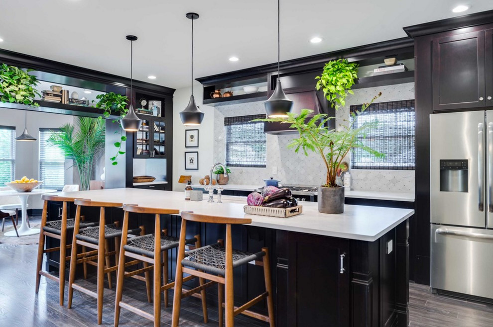 Example of a large transitional single-wall dark wood floor and brown floor eat-in kitchen design in DC Metro with an undermount sink, dark wood cabinets, solid surface countertops, stone tile backsplash, stainless steel appliances, an island, recessed-panel cabinets, white backsplash and white countertops