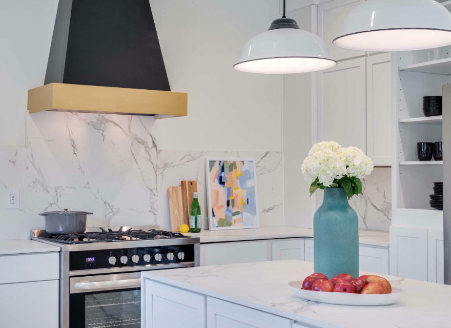 Example of a mid-sized transitional single-wall light wood floor and beige floor enclosed kitchen design in DC Metro with shaker cabinets, white cabinets, marble countertops, white backsplash, marble backsplash, stainless steel appliances, an island and an undermount sink