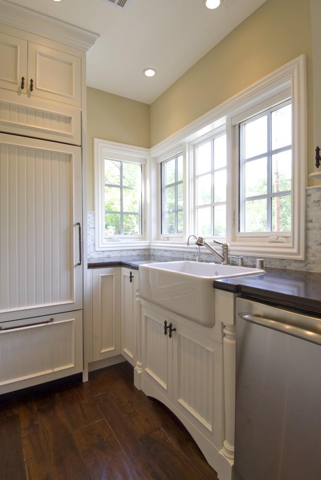 Elegant kitchen photo in San Francisco with paneled appliances, a farmhouse sink, recessed-panel cabinets, white cabinets, quartz countertops, white backsplash and stone tile backsplash