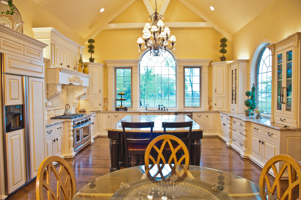 Example of a classic u-shaped eat-in kitchen design in Nashville with raised-panel cabinets, beige cabinets and paneled appliances