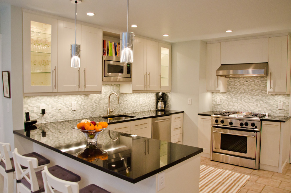 Example of a transitional kitchen design in New York with mosaic tile backsplash and stainless steel appliances