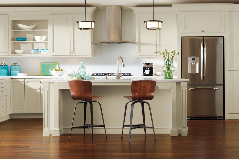 Mid-sized elegant l-shaped medium tone wood floor kitchen photo in Other with stainless steel appliances, an island, white countertops, recessed-panel cabinets, beige cabinets and white backsplash