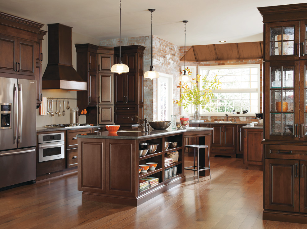 Example of a classic medium tone wood floor and brown floor kitchen design in Other with dark wood cabinets, stainless steel appliances, an island and gray countertops
