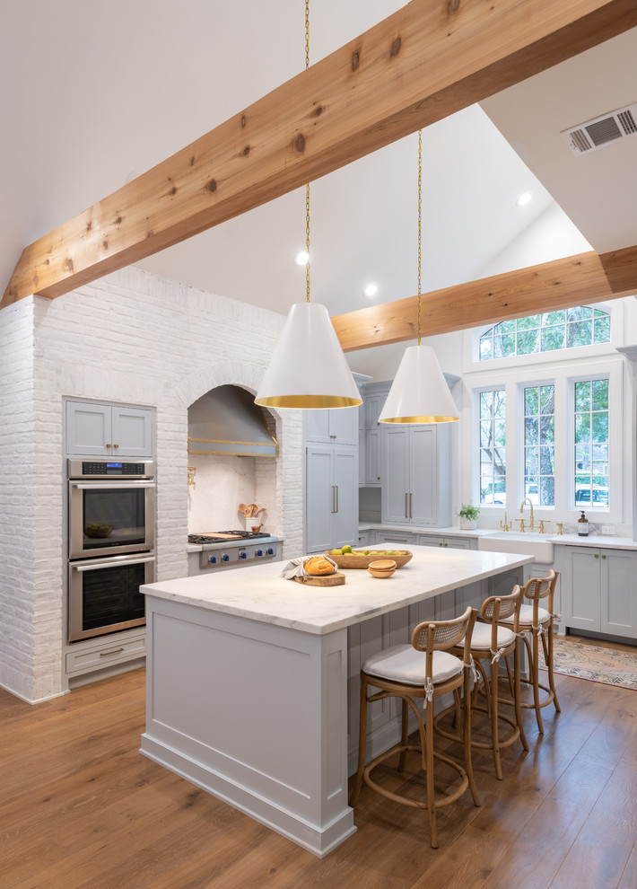 Cottage l-shaped medium tone wood floor and brown floor eat-in kitchen photo in Houston with a farmhouse sink, recessed-panel cabinets, gray cabinets, white backsplash, window backsplash, stainless steel appliances, an island and white countertops