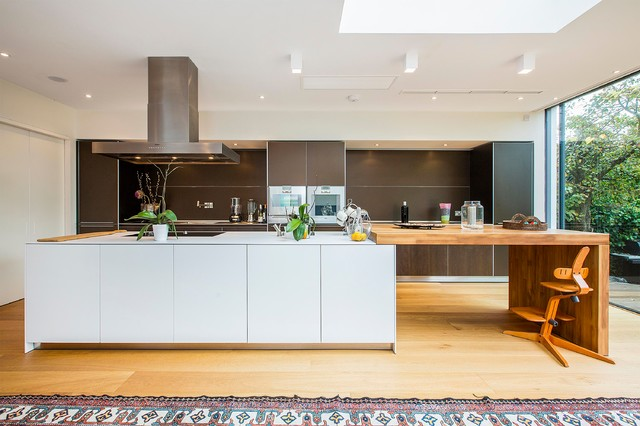Kitchen - modern galley light wood floor kitchen idea in London with flat-panel cabinets, dark wood cabinets, brown backsplash, paneled appliances and an island