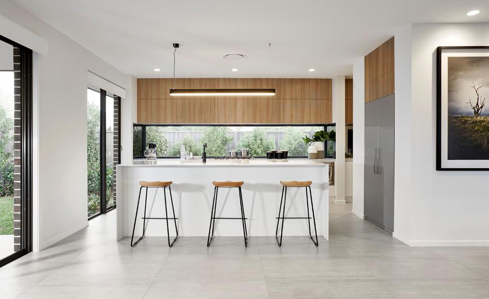 Réalisation d'une cuisine ouverte parallèle minimaliste avec un placard à porte plane, des portes de placard en bois brun, une crédence en fenêtre, un électroménager en acier inoxydable, un îlot central et un sol gris.