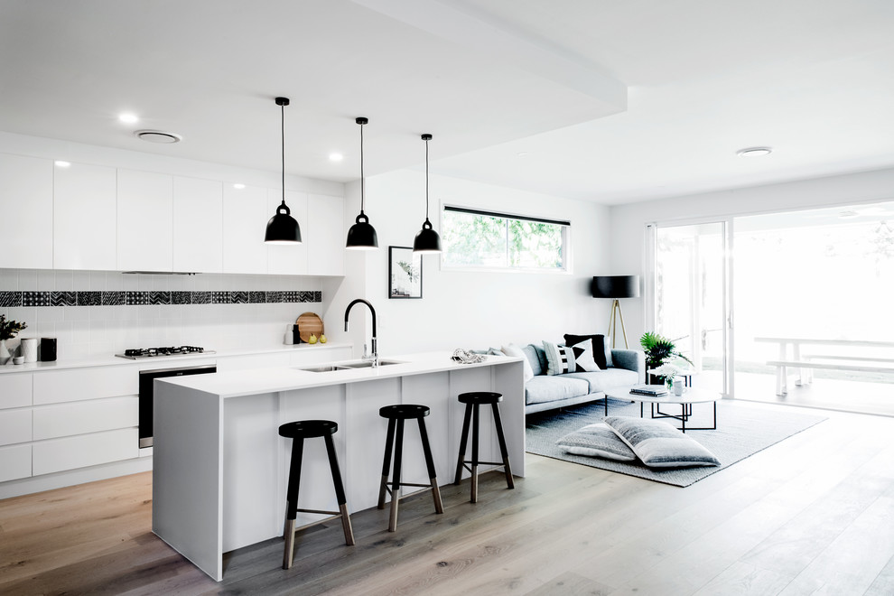 Open concept kitchen - scandinavian galley light wood floor and beige floor open concept kitchen idea in Brisbane with a double-bowl sink, flat-panel cabinets, white backsplash, black appliances and an island