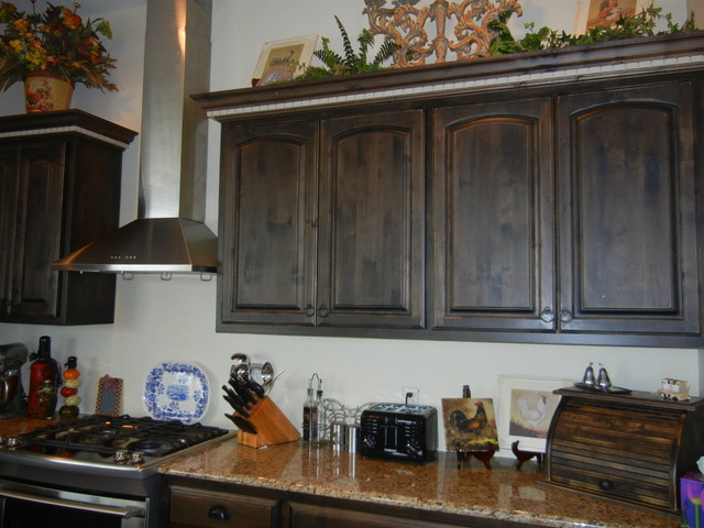 Distressed black walnut stain with cream island for Black stained cabinets