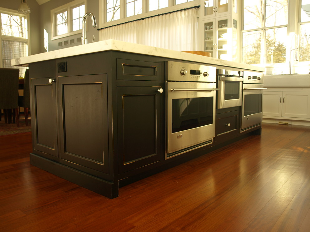 Eat-in kitchen - mid-sized contemporary u-shaped dark wood floor and brown floor eat-in kitchen idea in New York with a farmhouse sink, recessed-panel cabinets, white cabinets, solid surface countertops, white backsplash, paneled appliances, an island and marble backsplash