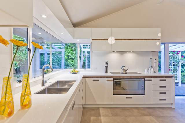 Open concept kitchen - contemporary u-shaped white floor open concept kitchen idea in Los Angeles with a double-bowl sink, flat-panel cabinets, white cabinets, solid surface countertops, white backsplash, glass sheet backsplash, stainless steel appliances and a peninsula