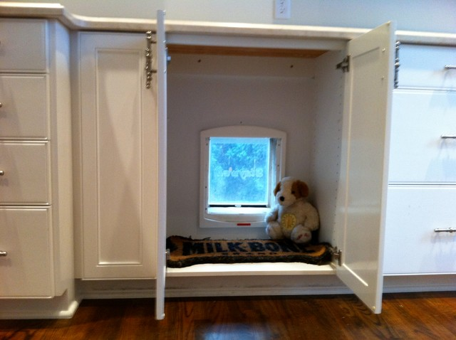 Doggie door hidden in cabinet goes out to dog run for Huzz house