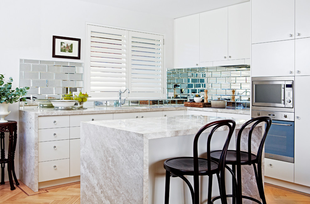 Inspiration for a transitional l-shaped light wood floor kitchen remodel in Sydney with an undermount sink, flat-panel cabinets, white cabinets, metallic backsplash, subway tile backsplash, stainless steel appliances and an island