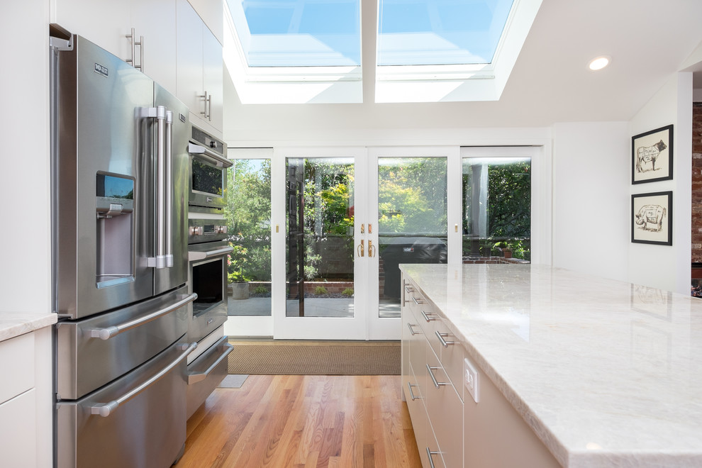 Inspiration for a large transitional l-shaped medium tone wood floor kitchen pantry remodel in Portland with an undermount sink, flat-panel cabinets, medium tone wood cabinets, quartzite countertops, white backsplash, ceramic backsplash, stainless steel appliances and an island