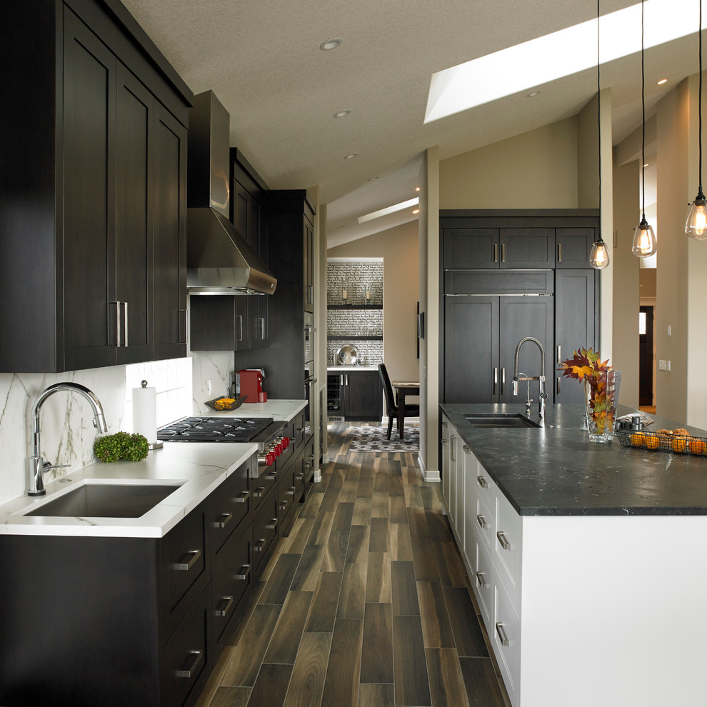 Minimalist l-shaped porcelain tile open concept kitchen photo in Calgary with an undermount sink, shaker cabinets, dark wood cabinets, granite countertops, white backsplash, stone slab backsplash, stainless steel appliances and an island