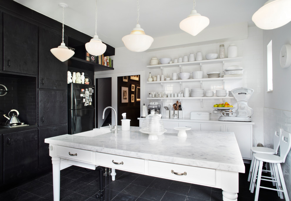 Inspiration for a contemporary kitchen remodel in Toronto with subway tile backsplash, black appliances, marble countertops, flat-panel cabinets, black cabinets and white backsplash
