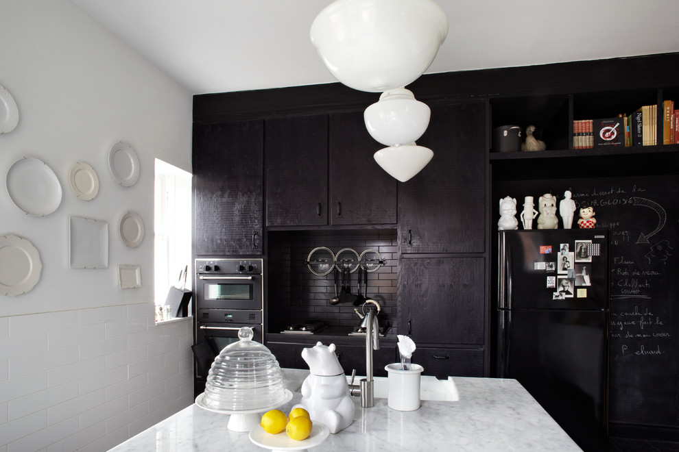 Inspiration for a contemporary kitchen remodel in Toronto with a farmhouse sink, flat-panel cabinets, black cabinets, black backsplash, subway tile backsplash, black appliances and an island