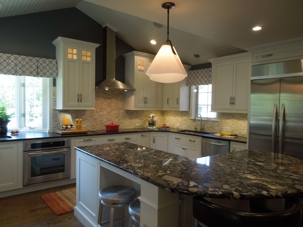 Elegant u-shaped eat-in kitchen photo in Boston with an undermount sink, shaker cabinets, white cabinets, granite countertops, multicolored backsplash and stainless steel appliances