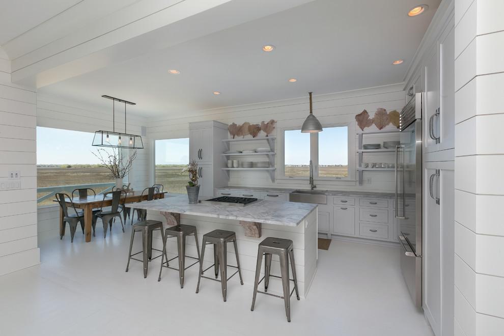 Idee per una cucina stile marino con lavello stile country, ante in stile shaker, ante bianche, paraspruzzi bianco e elettrodomestici in acciaio inossidabile
