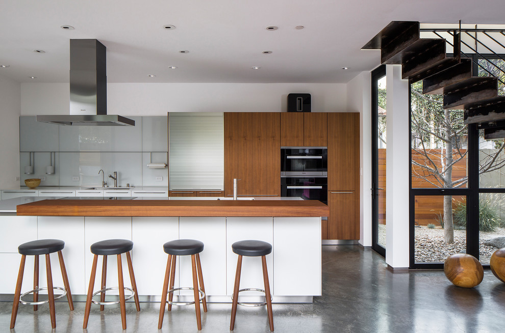 Inspiration for a modern galley concrete floor and gray floor eat-in kitchen remodel in Los Angeles with a single-bowl sink, flat-panel cabinets, medium tone wood cabinets, gray backsplash, glass sheet backsplash, black appliances and an island