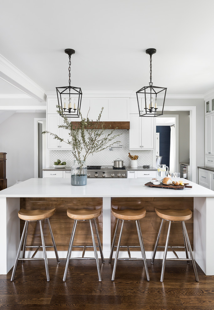 Large beach style medium tone wood floor and brown floor eat-in kitchen photo in Chicago with an undermount sink, beaded inset cabinets, white cabinets, quartz countertops, white backsplash, ceramic backsplash, stainless steel appliances, an island and white countertops