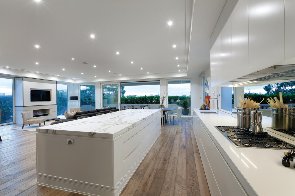 Minimalist open concept kitchen photo in Melbourne with flat-panel cabinets, white cabinets, marble countertops and mirror backsplash