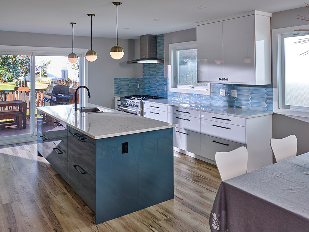 Example of a 1960s beige floor kitchen design in Edmonton with an undermount sink, flat-panel cabinets, blue backsplash, stainless steel appliances and an island