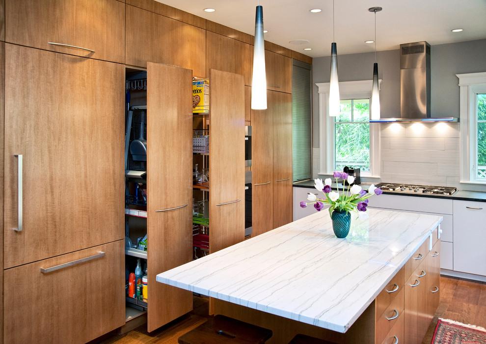Mid-sized trendy medium tone wood floor kitchen photo in Boston with flat-panel cabinets, medium tone wood cabinets, marble countertops, white backsplash, porcelain backsplash and stainless steel appliances