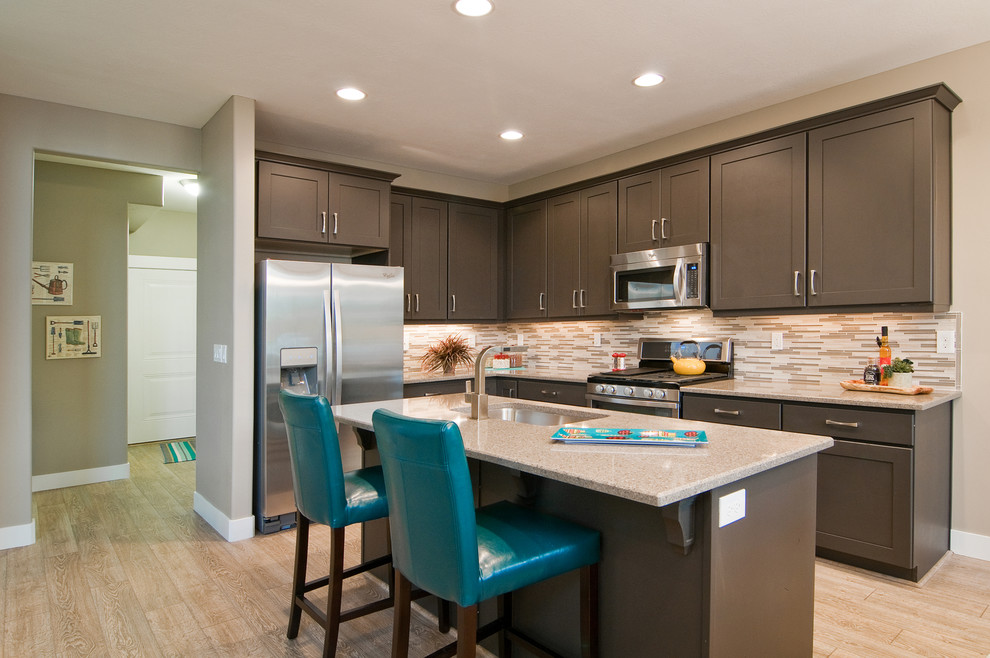 Inspiration for a contemporary l-shaped light wood floor open concept kitchen remodel in Salt Lake City with stainless steel appliances, an undermount sink, shaker cabinets, brown cabinets, granite countertops, beige backsplash and an island