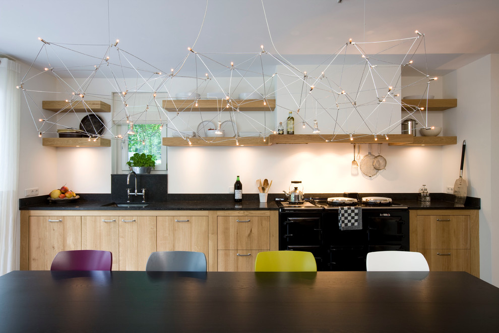 Inspiration for a contemporary kitchen remodel in New York with flat-panel cabinets, black appliances and light wood cabinets