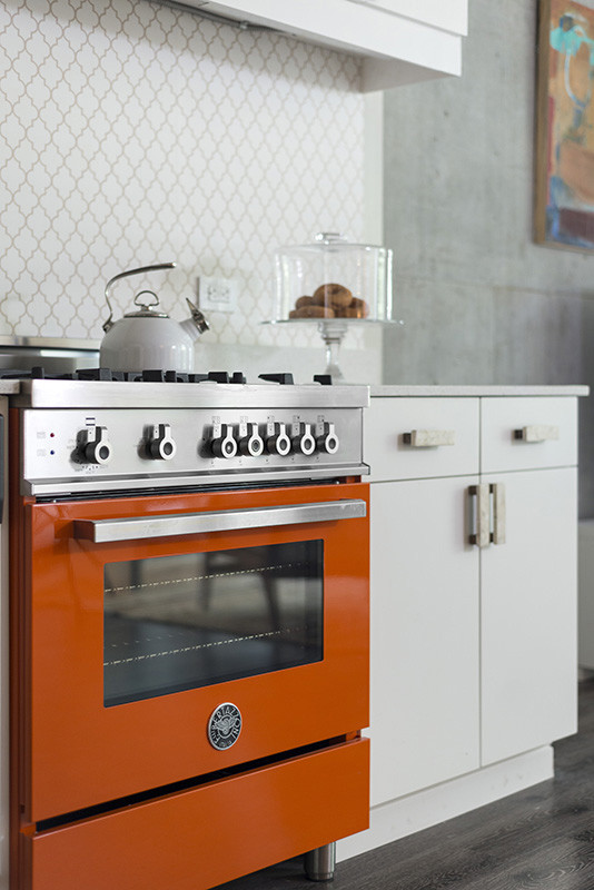 Open concept kitchen - mid-sized industrial l-shaped medium tone wood floor open concept kitchen idea in Los Angeles with a farmhouse sink, flat-panel cabinets, white cabinets, quartz countertops, white backsplash, colored appliances and an island