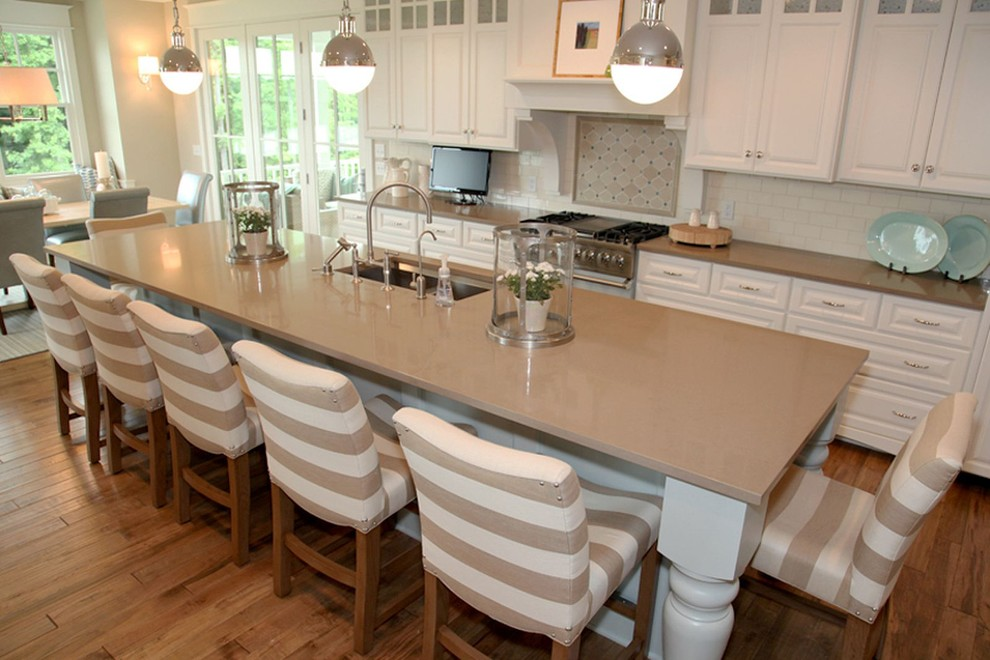 Example of a transitional eat-in kitchen design in Grand Rapids with an undermount sink, raised-panel cabinets, white cabinets, quartz countertops, white backsplash and subway tile backsplash