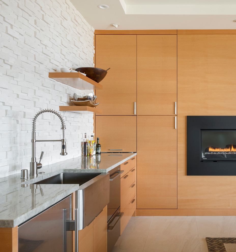 Kitchen - contemporary kitchen idea in Seattle with a farmhouse sink, stainless steel appliances, flat-panel cabinets, medium tone wood cabinets, white backsplash and stone tile backsplash