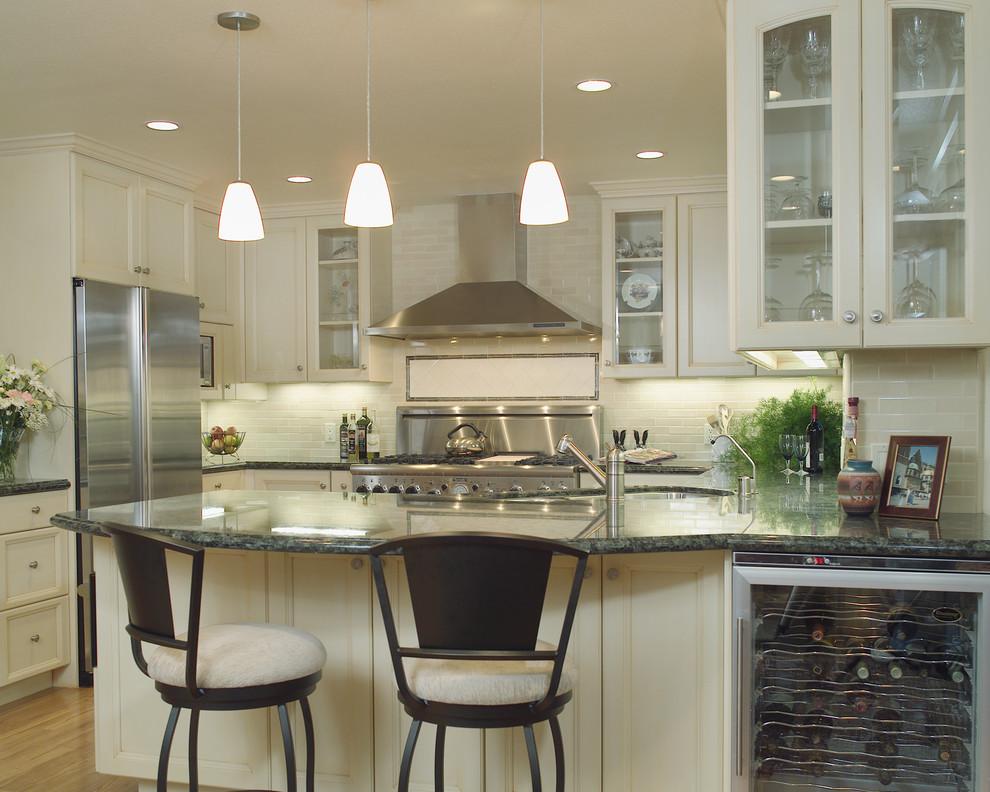 Elegant u-shaped kitchen photo in San Francisco with glass-front cabinets, stainless steel appliances, granite countertops, an undermount sink, beige cabinets, beige backsplash and subway tile backsplash