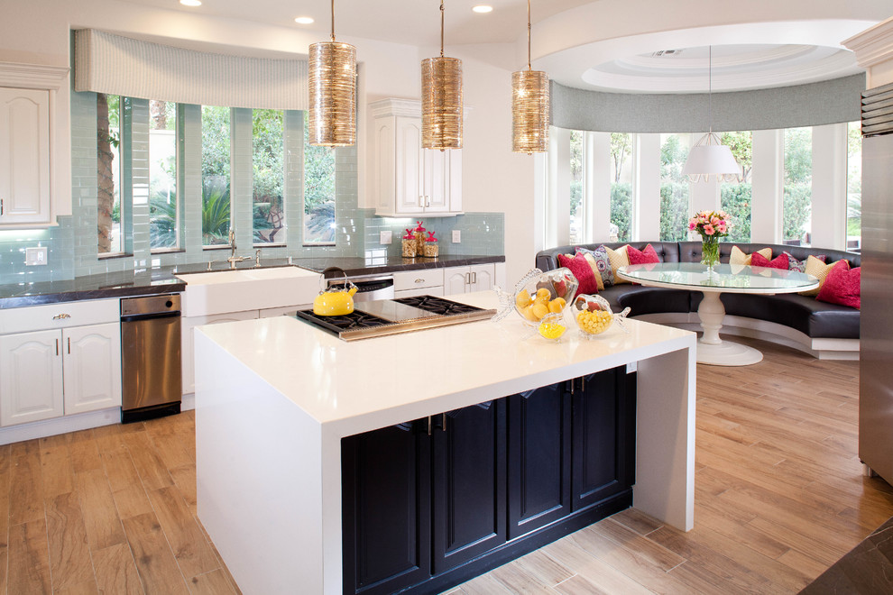 Eat-in kitchen - contemporary light wood floor eat-in kitchen idea in Las Vegas with a farmhouse sink, raised-panel cabinets, white cabinets, blue backsplash and an island