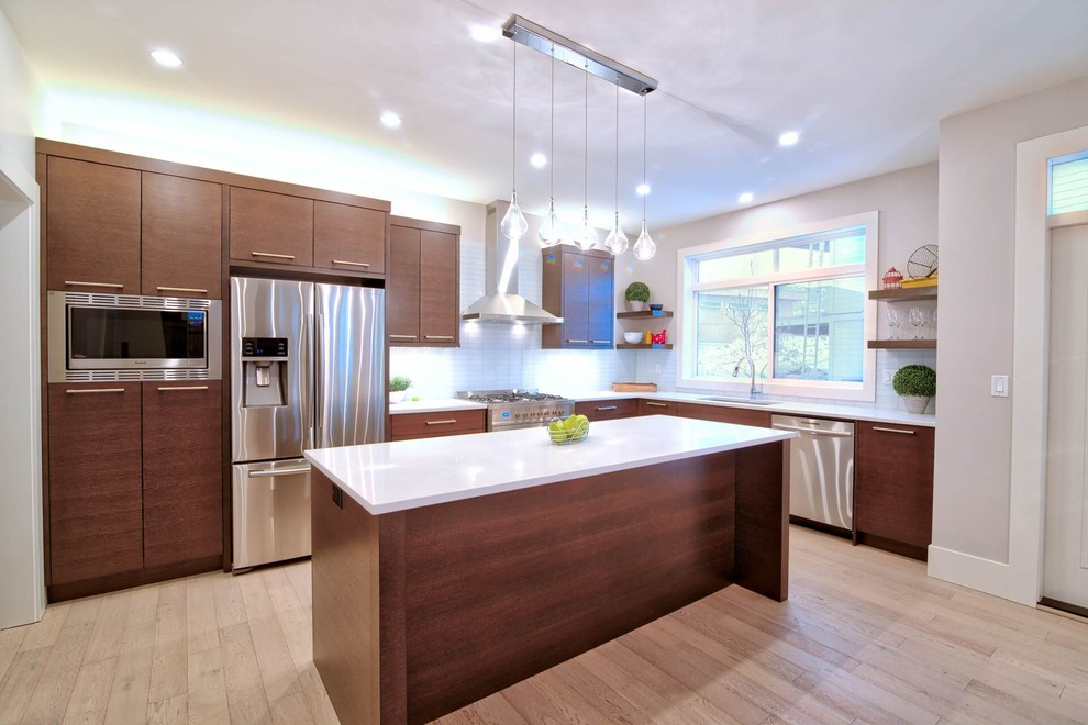 Open concept kitchen - large modern l-shaped light wood floor open concept kitchen idea in Vancouver with an undermount sink, flat-panel cabinets, dark wood cabinets, quartz countertops, white backsplash, glass tile backsplash, stainless steel appliances and an island