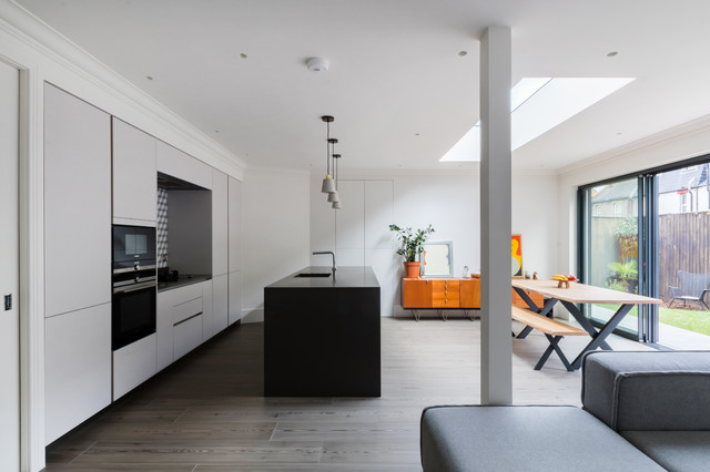 Medium sized contemporary single-wall kitchen/diner in London with a submerged sink, flat-panel cabinets, grey cabinets, multi-coloured splashback, ceramic splashback, stainless steel appliances, light hardwood flooring, an island, grey floors and black worktops.