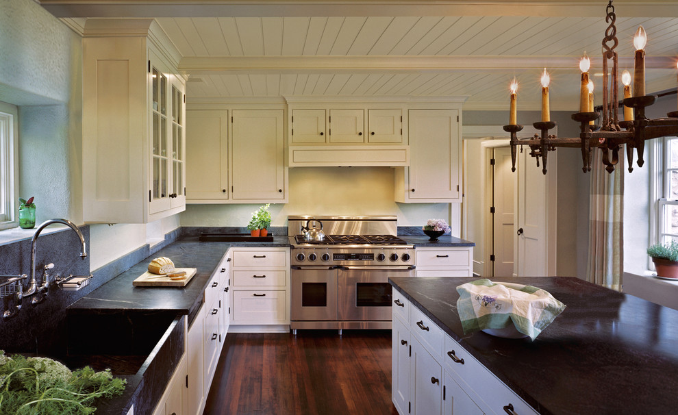 Cottage medium tone wood floor and brown floor enclosed kitchen photo in DC Metro with a farmhouse sink, shaker cabinets, beige cabinets, stainless steel appliances, soapstone countertops, white backsplash and black countertops