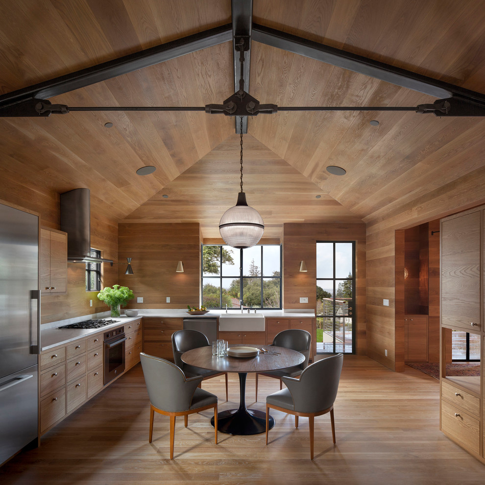 Large mountain style l-shaped medium tone wood floor and beige floor eat-in kitchen photo in San Francisco with flat-panel cabinets, medium tone wood cabinets, stainless steel appliances, a farmhouse sink, brown backsplash, wood backsplash and no island