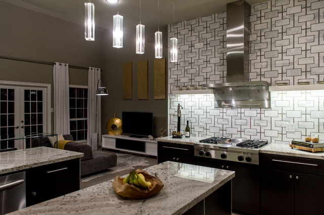 Eat-in kitchen - mid-sized contemporary u-shaped limestone floor eat-in kitchen idea in New Orleans with an integrated sink, flat-panel cabinets, black cabinets, granite countertops, multicolored backsplash, stainless steel appliances and an island