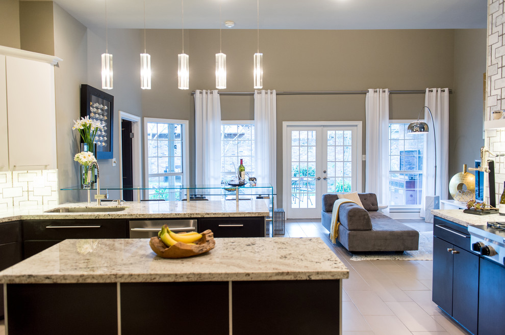 Inspiration for a mid-sized contemporary u-shaped limestone floor eat-in kitchen remodel in New Orleans with an integrated sink, flat-panel cabinets, black cabinets, granite countertops, multicolored backsplash, stainless steel appliances and an island