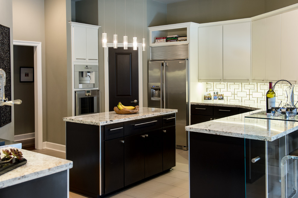 Example of a mid-sized trendy u-shaped limestone floor eat-in kitchen design in New Orleans with an integrated sink, flat-panel cabinets, white cabinets, granite countertops, multicolored backsplash, stainless steel appliances and an island