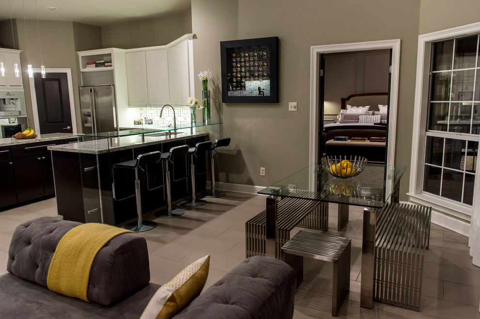 Example of a mid-sized trendy u-shaped limestone floor eat-in kitchen design in New Orleans with an integrated sink, flat-panel cabinets, black cabinets, granite countertops, multicolored backsplash, stainless steel appliances and an island