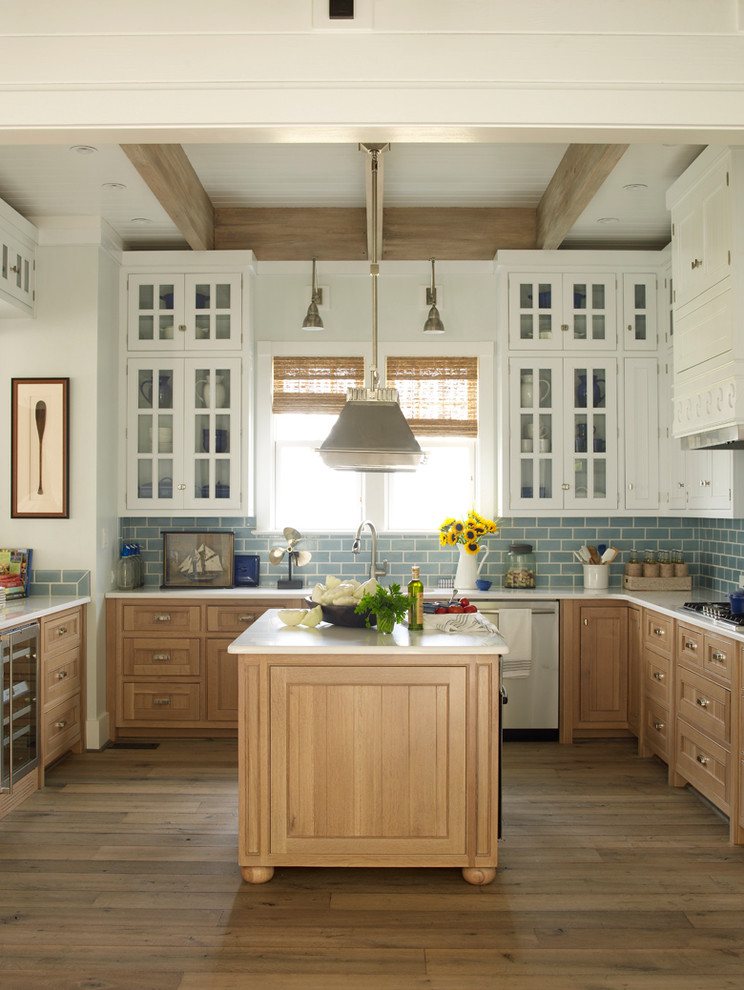 Example of a beach style light wood floor kitchen design in Jacksonville with marble countertops, blue backsplash, subway tile backsplash, stainless steel appliances, an island, glass-front cabinets and white cabinets