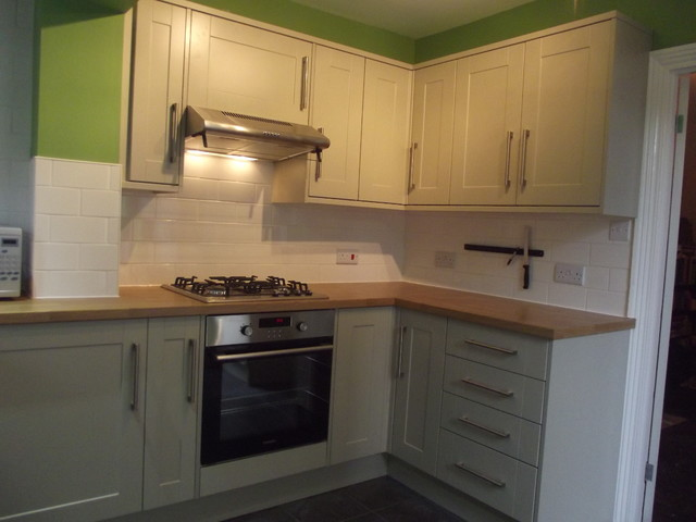 Design ideas for a medium sized classic u-shaped enclosed kitchen in London with a single-bowl sink, shaker cabinets, grey cabinets, laminate countertops, white splashback, ceramic splashback, stainless steel appliances, ceramic flooring and no island.