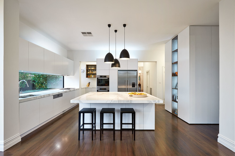 Kitchen - contemporary u-shaped dark wood floor kitchen idea in Melbourne with a double-bowl sink, flat-panel cabinets, white cabinets, stainless steel appliances and an island